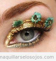 Maquillaje de ojos dorado con flores en las pestañas