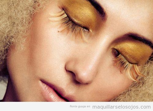 Maquillaje de ojos dorado y con plumas que simula el sol